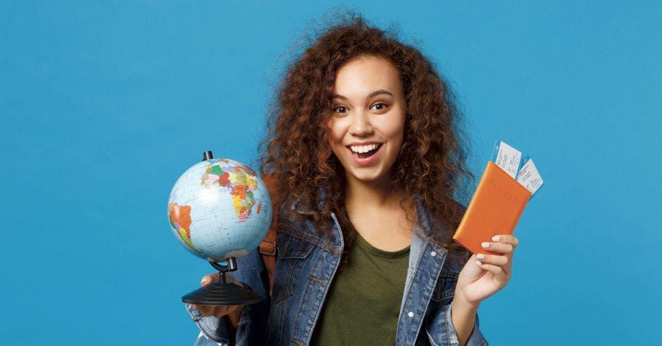 una mujer sonriente con dos boletos en la mano y un globo terráqueo