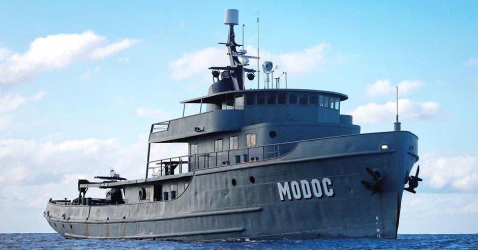 un buque grande color gris con la leyenda Modoc escrita en un costado