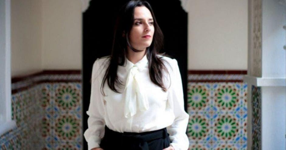 muje de cabello obscuro, blusa blanca y pantalón negro