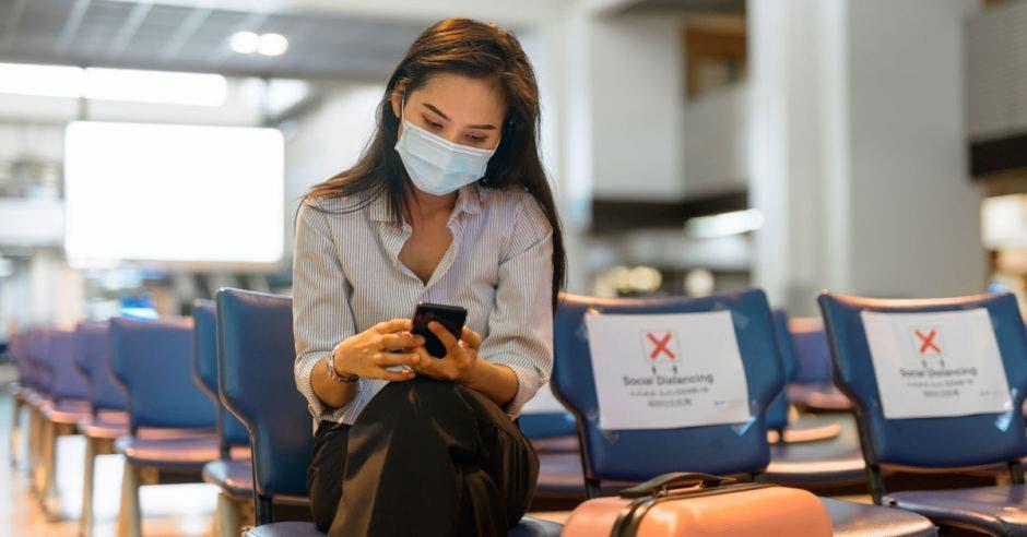 una mujer revisa su celular en el lobby de un aeropuerto