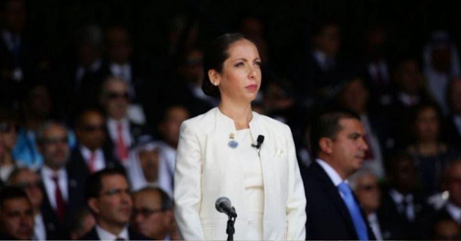 mujer joven con saco y blusa blanca de pie frente a un micrófono