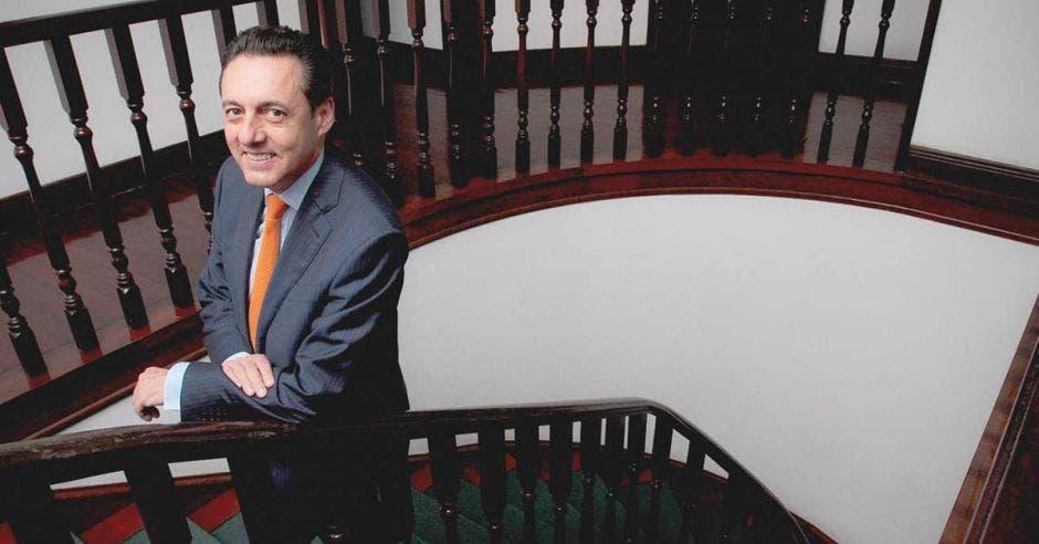 hombre de traje azul, corbata naranja y cabello obscuro parado en escaleras