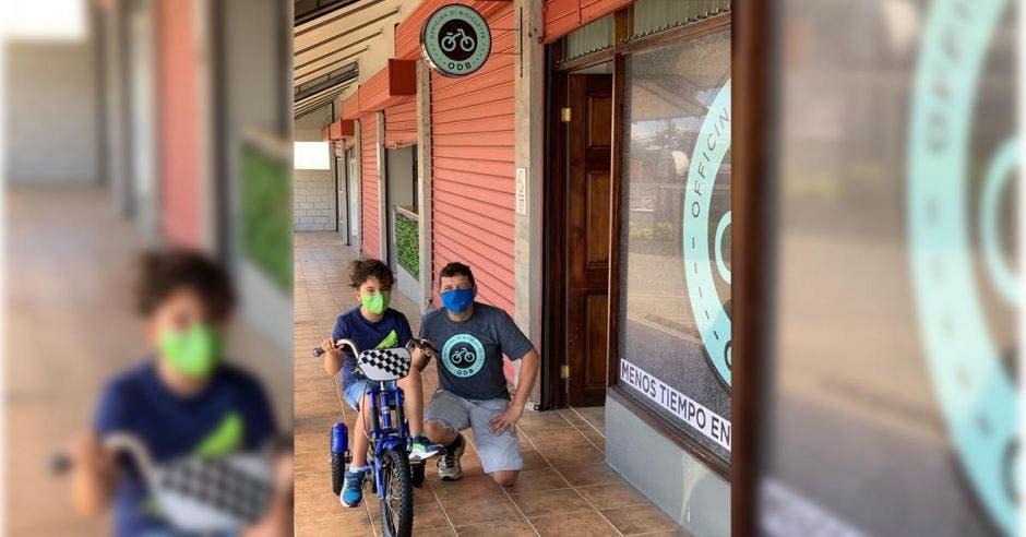 Un niño en triciclo junto a un hombre de cuclillas