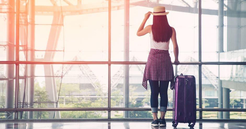 una mujer con una valija púrpura en una sala de espera