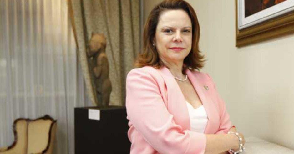 mujer de cabello castaño con saco rosa cruzada de brazos