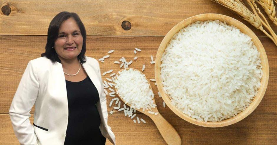 una mujer de blaser blanco y traje negro junto a una cuchara y un tazón lleno de arroz