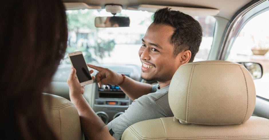 Persona manejando y viendo el celular