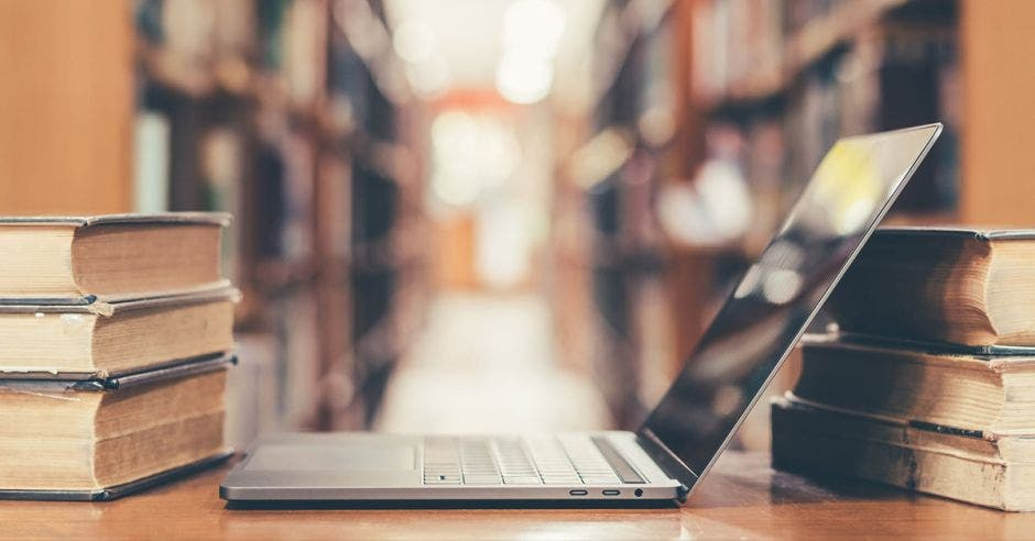 laptop abierta en medio de libros