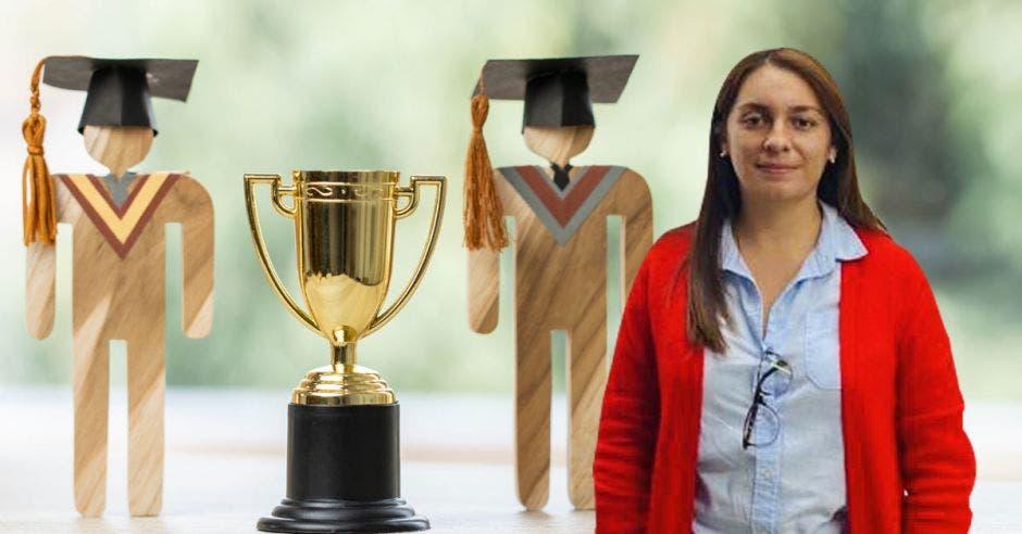 mujer con sueter rojo y camisa azul de fondo muñecos de madera con birretes y en medio un trofeo dorado