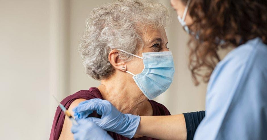 una mujer adulta mayor recibe la vacuna de Covid-19