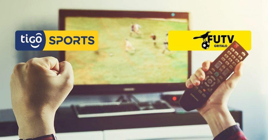 dos personas sostienen un control remoto sobre sus cabezas. Ambas miran un televisor.