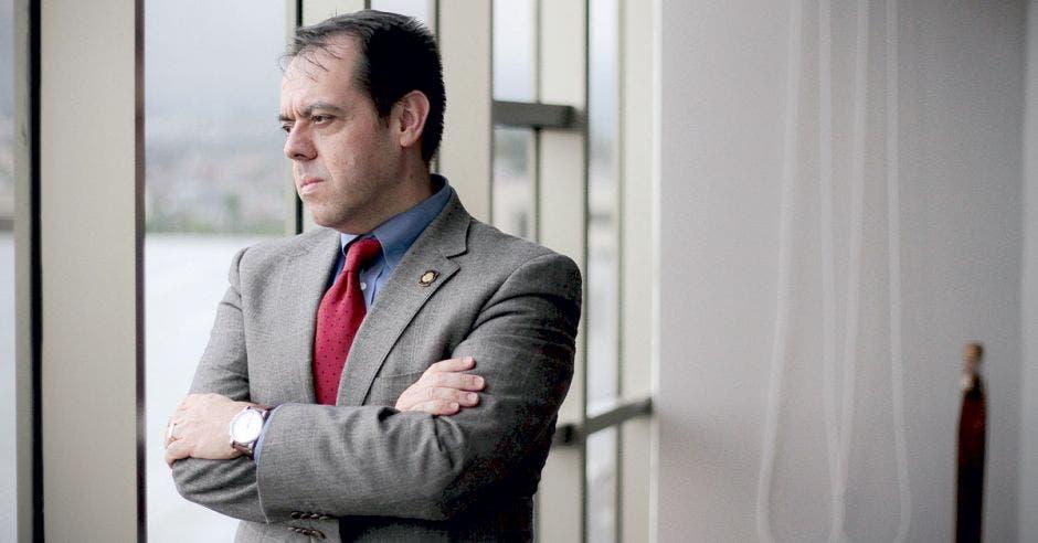 un hombre de saco gris, camisa azul y corbata roja
