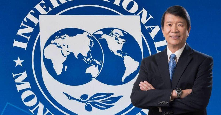 uun hombre de saco y corbata sobre un fondo del logo del fondo monetario internacional
