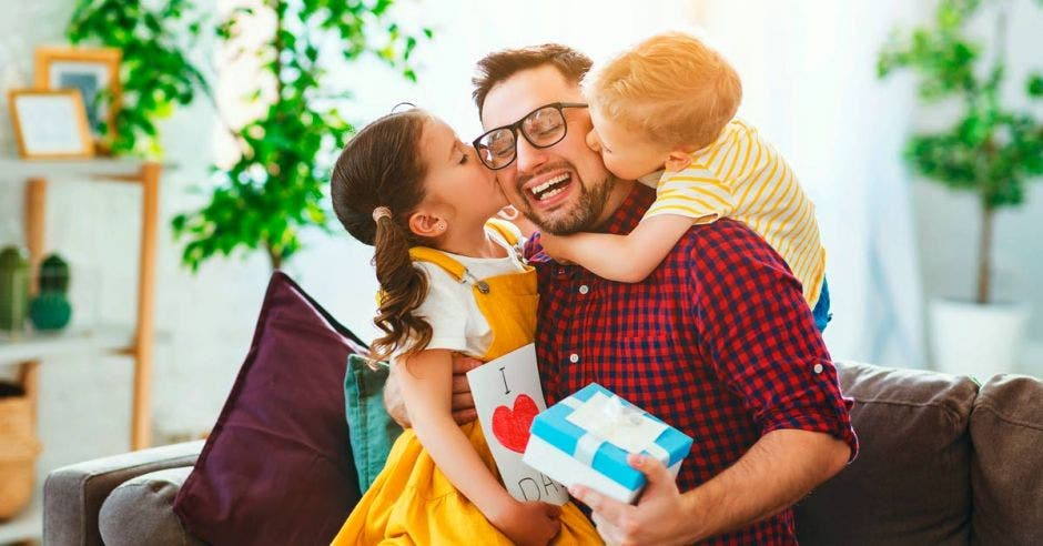 un papá con sus dos hijos abriendo un regalo del Día del Padre