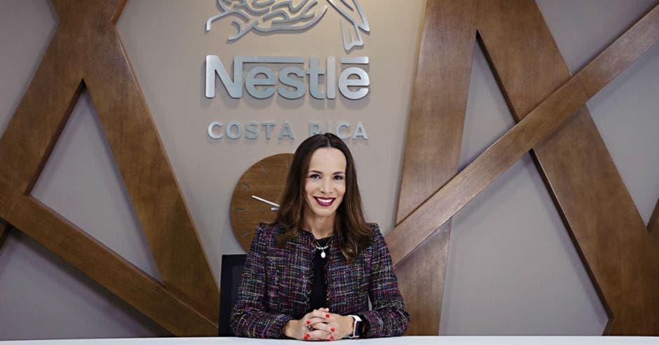 una mujer de traje entero con vista de frente y debajo de un letrero que dice Nestlé