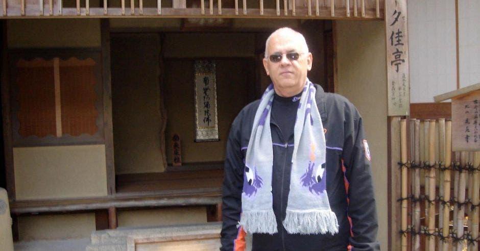 hombre calvo de lentes obscuros, chamarra negra y bufanda