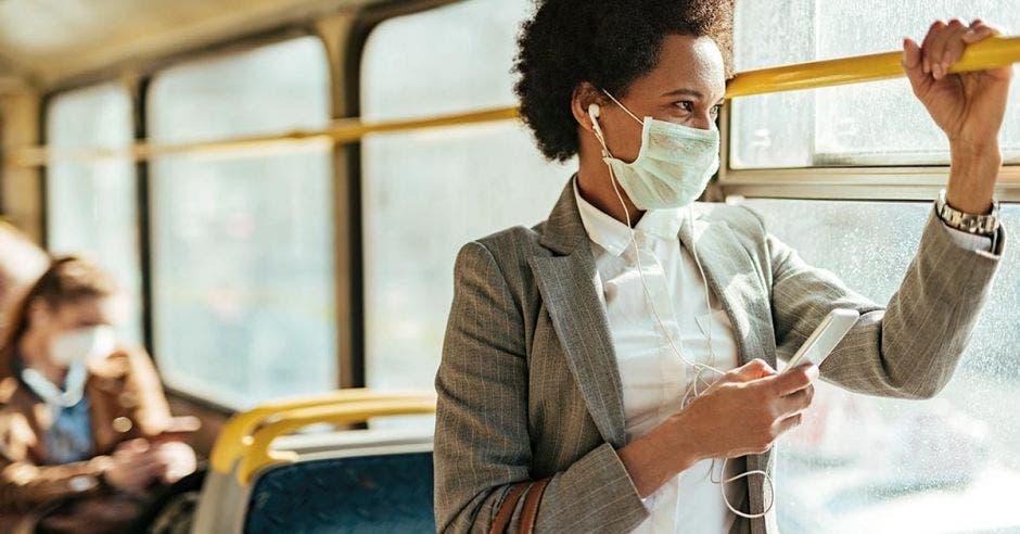 mujer de cabello negro corto con mascarilla, saco gris y camisa blanca en transporte público