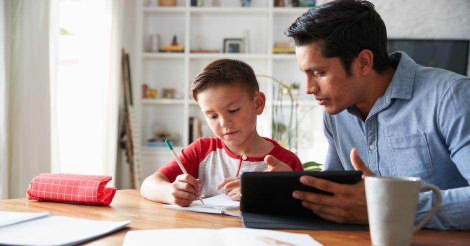 niño sentado escribiendo y adulto junto a él sosteniendo una tablet