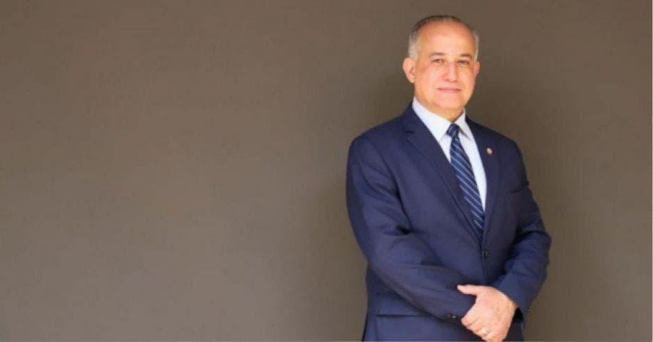 hombre calvo de traje azul marino y corbata azul con las manos sostenidas al frente