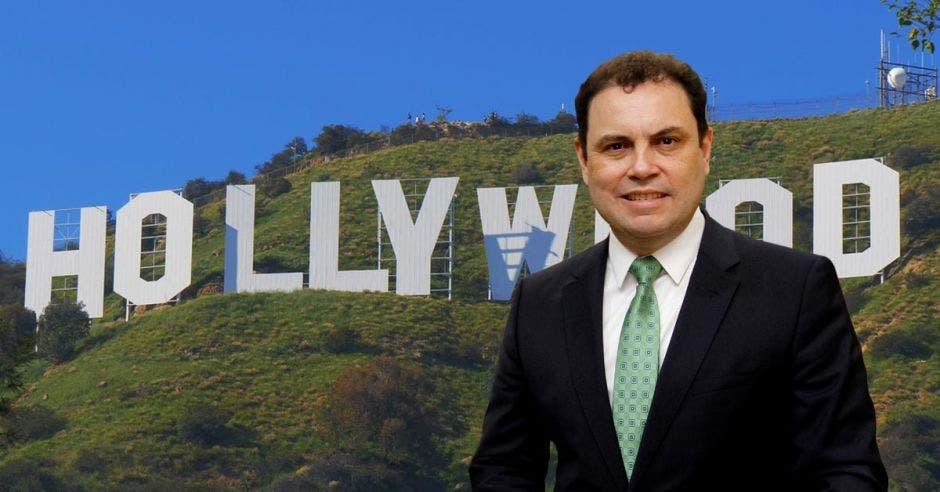 un hombre de saco y corbata sobre el letrero de Holywood