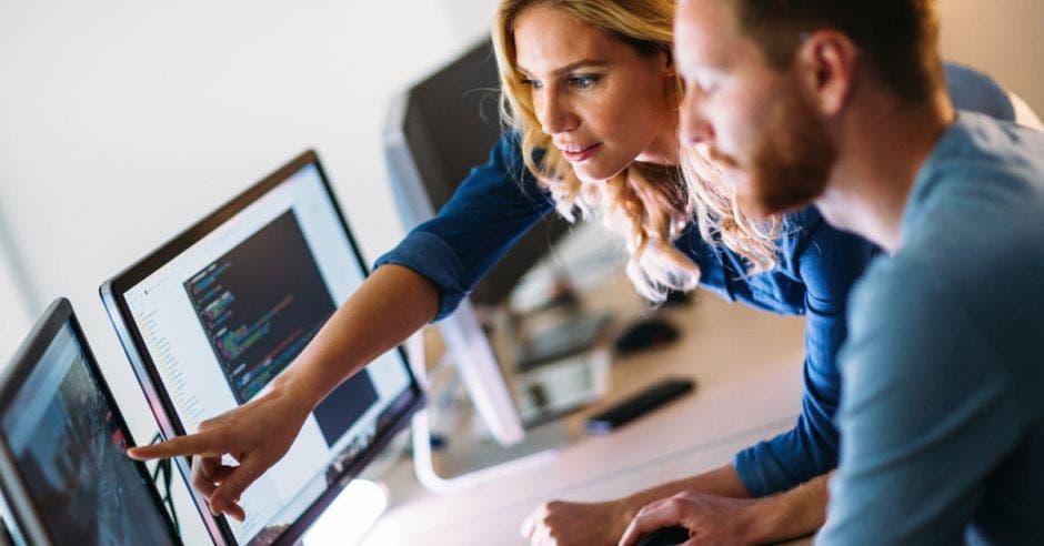 una mujer le da instrucciones a un joven en una computadora