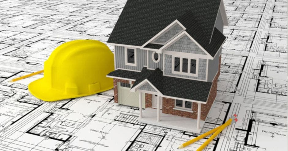casco, maqueta de casa y dos lápices sobre planos de construcción