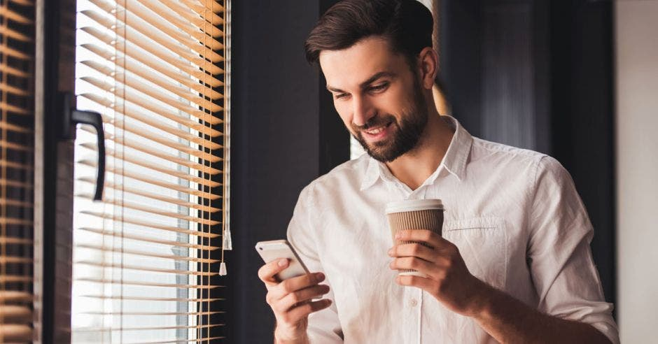Un hombre con un celular en su mano y un café en la otra