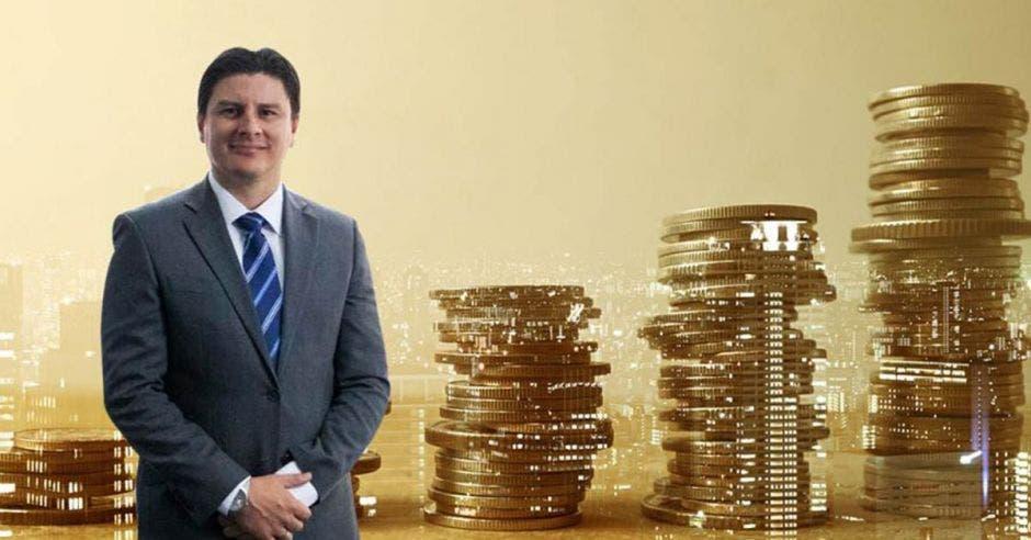 hombre de cabello negro, traje gris y corbata azul junto a imagen de torres de monedas