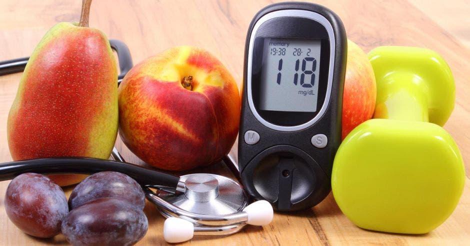 Unas frutas, un estetoscopio, una pesa y un aparato para medir el azúcar en la sangre
