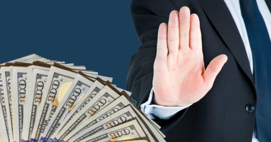 hombre con traje levantando la mano junto a billetes