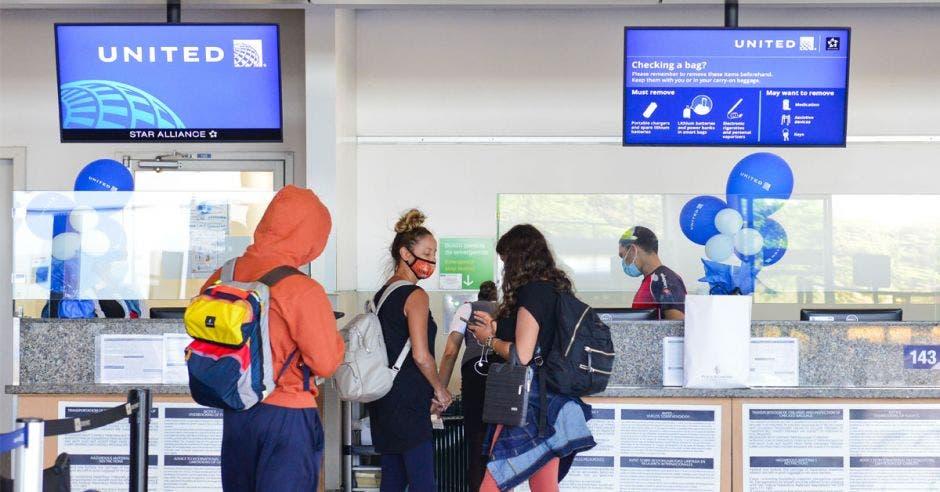 un grupo de personas espera ser atendida en el counter de United Airlines en el aeropuerto