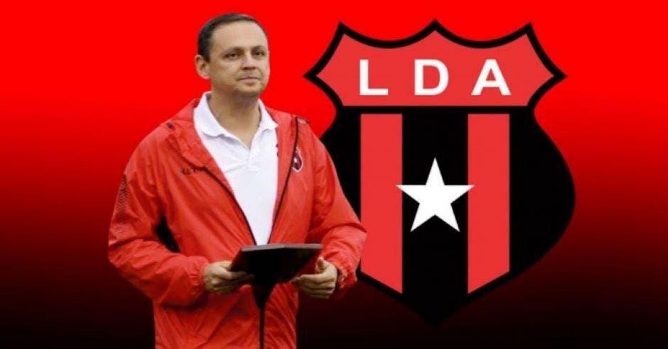hombre con chamarra roja y playera blanca detrás logotipo de Alajuelense