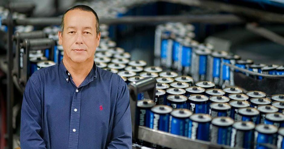 Un hombre de camisa azul y pantalón caqui sobre un fondo de baterías