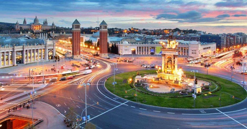 una ciudad iluminada, con un monumento dorado en el centro de una plaza