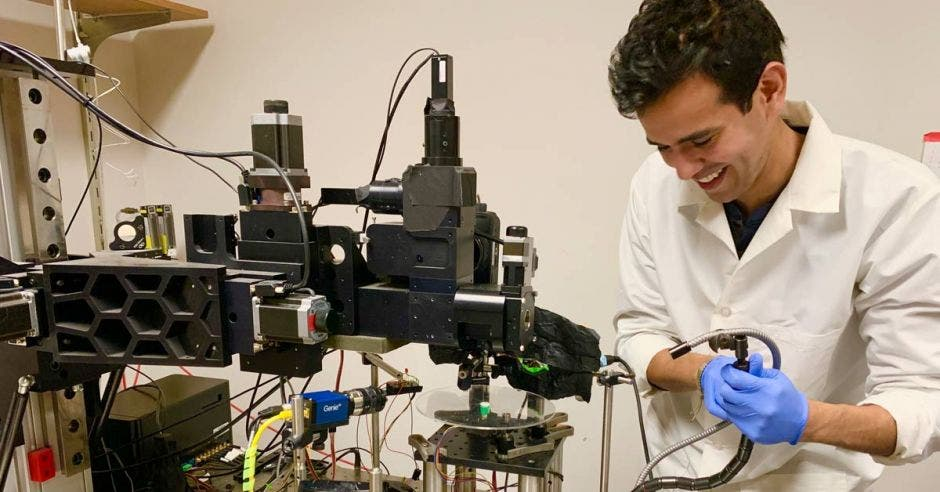 un hombre con bata manipula equipo de laboratorio