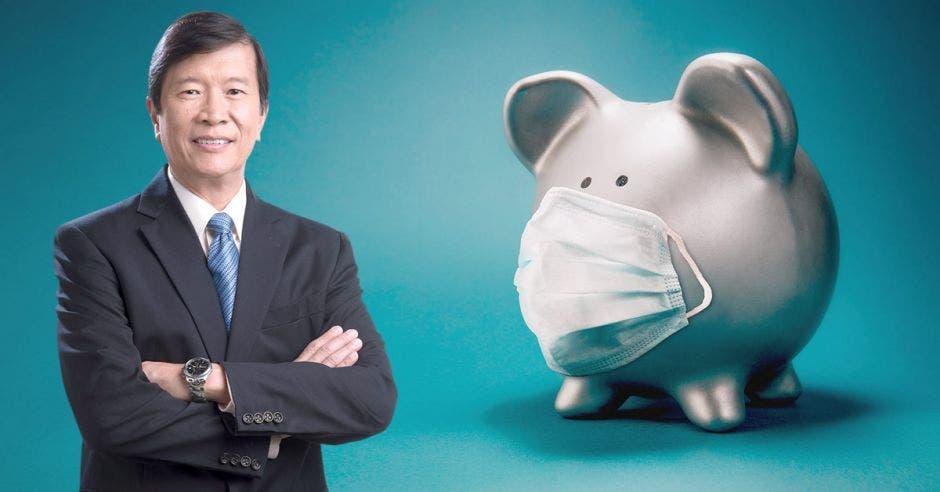 un hombre asiático con saco y corbata junto a una alcancía cubierta con una mascarilla