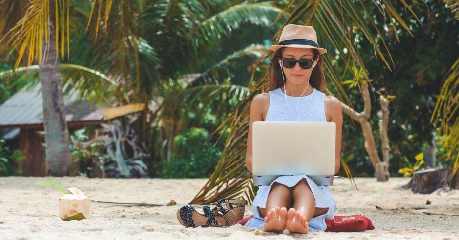 Joven mujer en vestido, gafas de sol y sombrero, trabajando en laptop en la playa, en el fondo de las palmeras