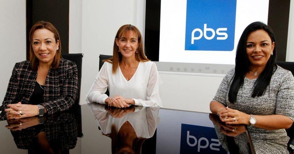 tres mujeres sentadas en una mesa, con el logo de PBS de fondo