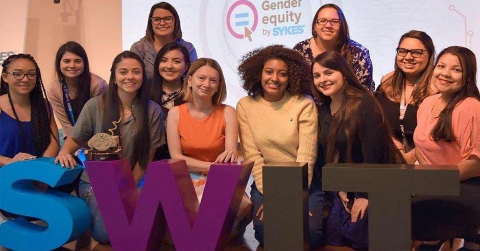 un grupo de mujeres posa junto a letrero que dice Swit