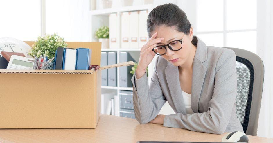 Mujer de gris triste con caja con sus cosas