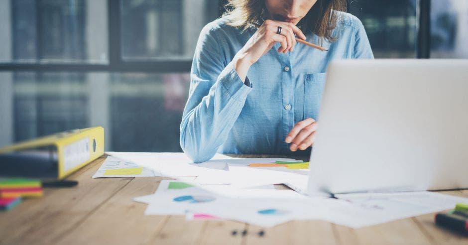 una mujer con blusa celeste escribe en una computadora