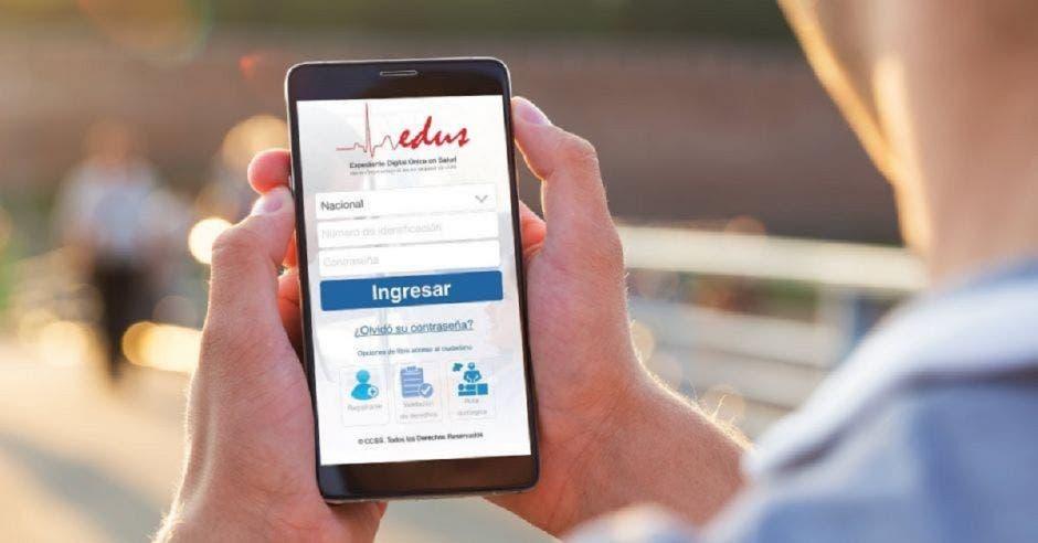 Una persona sosteniendo un celular en sus manos con el app del EDUS