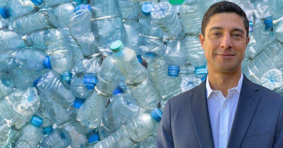 un hombre con saco sobre un fondo de botellas de plástico
