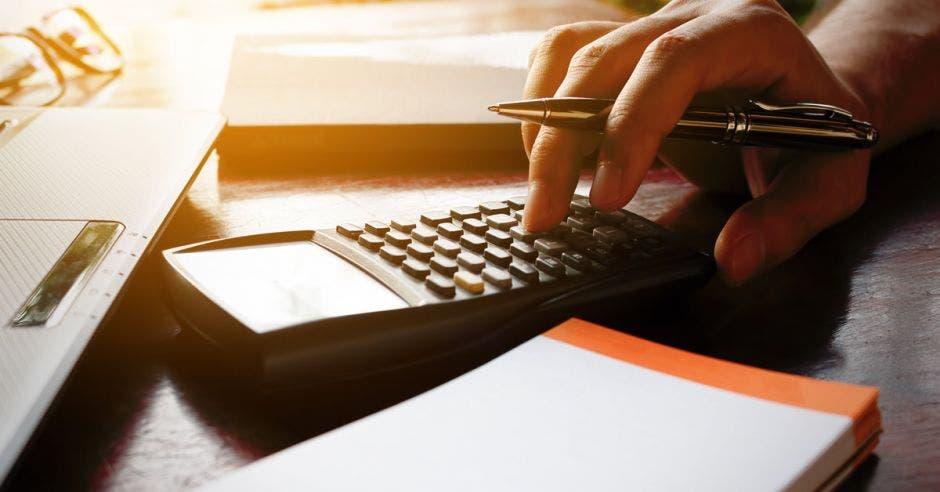 persona usando calculadora para elaborar presupuesto