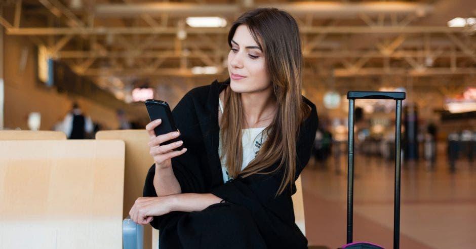 Concepto de viaje aéreo con una joven mujer informal sentada con maleta de equipaje de mano y revisando su celular