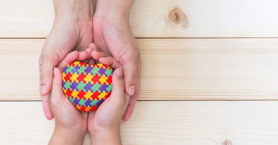 dos manos sostienen un corazón de colores