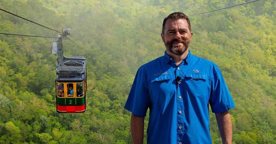 un hombre de camisa azul sobre el fondo de un teleférico en la naturaleza