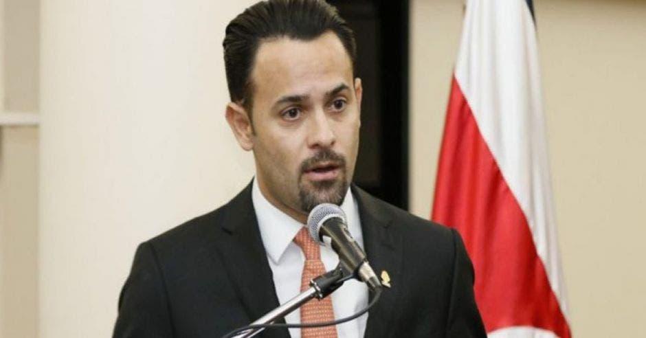 un hombre habla frente a un micrófono, con la bandera de Costa Rica de fondo