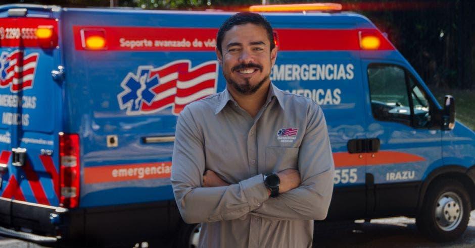hombre de cabello negro y barba, con camisa gris y brazos cruzados, detrás una ambulancia