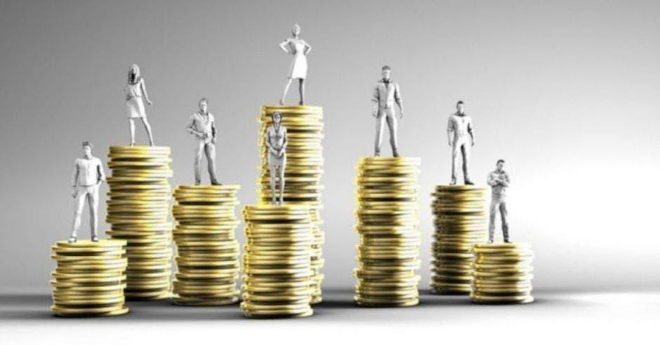 figuras plateadas de personas sobre torres de monedas